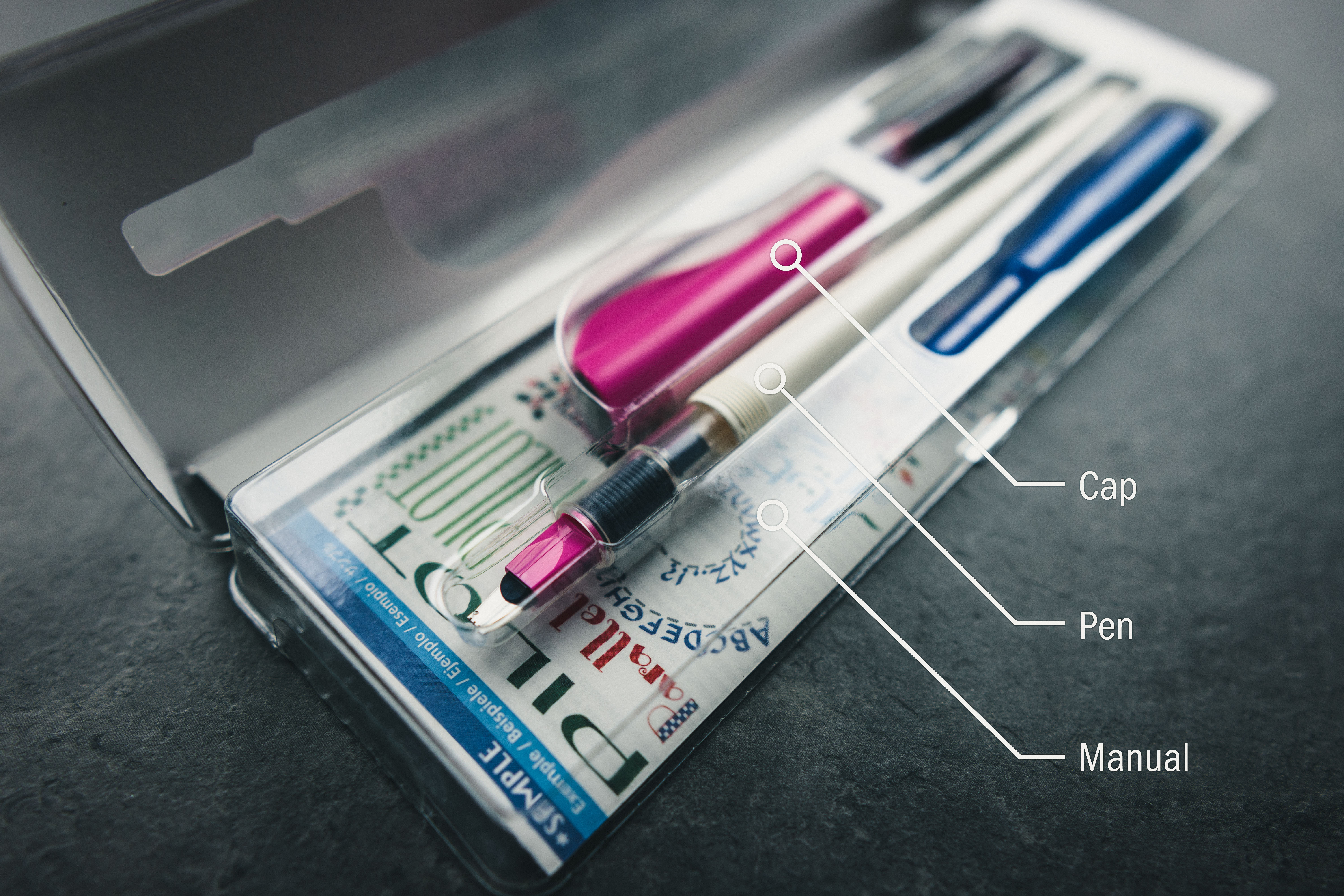Open 3mm pink Pilot Parallel pen retail box with top open and all parts inside resting on a grey countertop